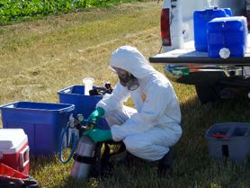 Photo of a person in full PPE, including fit tested respirator.